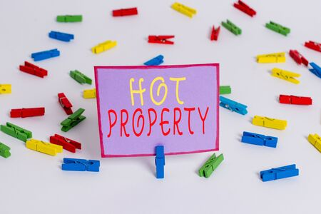 Conceptual hand writing showing Hot Property. Concept meaning Something which is sought after or is Heavily Deanalysisded Colored clothespin papers empty reminder white floor office Фото со стока