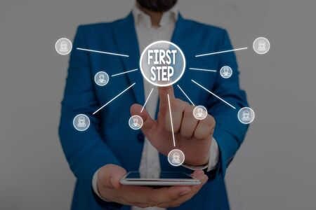 Text sign showing First Step. Business photo showcasing Pertaining to the start of a certain process or beginning Male human wear formal work suit presenting presentation using smart device