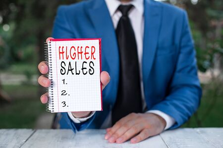 Text sign showing Higher Sales. Business photo text The average sold products and services of a company has grown Man holds empty paper with copy space in front of him