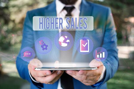 Word writing text Higher Sales. Business photo showcasing The average sold products and services of a company has grown Male human wear formal work suit presenting presentation using smart device