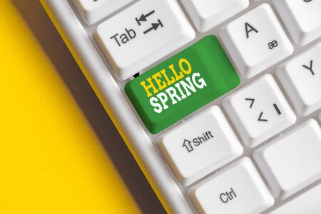 Conceptual hand writing showing Hello Spring. Concept meaning Welcoming the season after the winter Blossoming of flowers White pc keyboard with note paper above the white background
