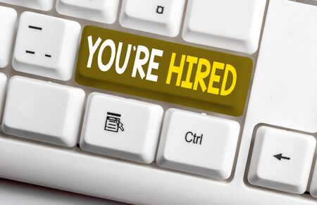 Conceptual hand writing showing You Re Hired. Concept meaning New Job Employed Newbie Enlisted Accepted Recruited White pc keyboard with note paper above the white background