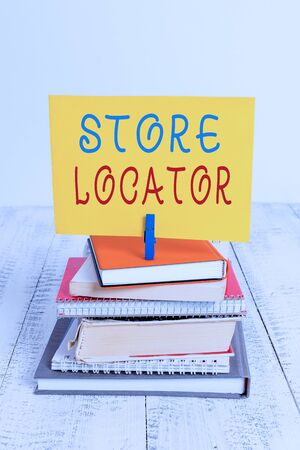 Conceptual hand writing showing Store Locator. Concept meaning to know the address contact number and operating hours pile stacked books notebook pin color reminder white wooden
