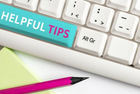 Handwriting text Helpful Tips. Conceptual photo Ask an Expert Solutions Hints Consulting Warning White pc keyboard with empty note paper above white background key copy space
