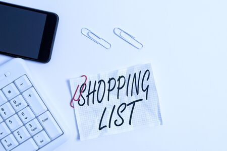 Text sign showing Shopping List. Business photo showcasing Discipline approach to shopping Basic Items to Buy White pc keyboard with empty note paper above white background and mobile phone Banco de Imagens