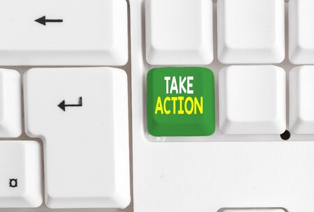 Conceptual hand writing showing Take Action. Concept meaning Supporting what you say not just words but through evidence White pc keyboard with note paper above the white background