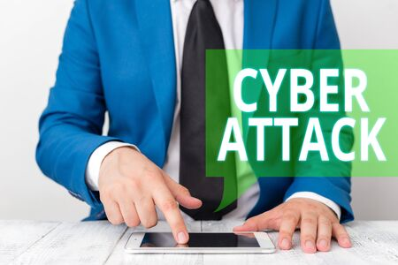 Conceptual hand writing showing Cyber Attack. Concept meaning An attempt by hackers to Damage Destroy a Computer System Businessman in blue suite with a tie holds lap top in hands 版權商用圖片