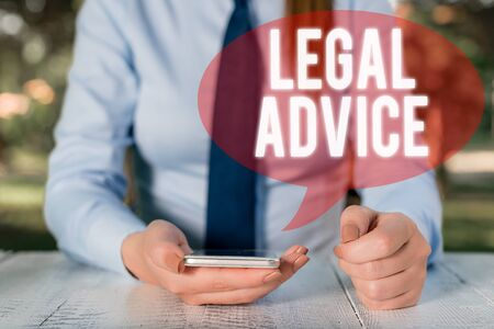 Writing note showing Legal Advice. Business concept for Lawyer opinion about law procedure in a particular situation Female business person sitting by table and holding mobile phone
