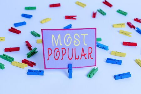 Conceptual hand writing showing Most Popular. Concept meaning Liked Followed Enjoyed by majority of the showing in a society Colored clothespin papers empty reminder white floor office 스톡 콘텐츠