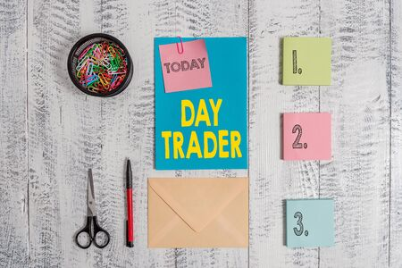 Word writing text Day Trader. Business photo showcasing A demonstrating that buy and sell financial instrument within the day Envelope letter sticky note ballpoint clips can scissors wooden background