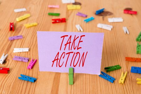Handwriting text Take Action. Conceptual photo Supporting what you say not just words but through evidence Colored clothespin papers empty reminder wooden floor background office