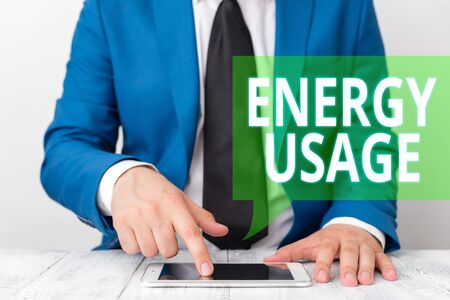 Conceptual hand writing showing Energy Usage. Concept meaning Amount of energy consumed or used in a process or system Businessman in blue suite with a tie holds lap top in hands