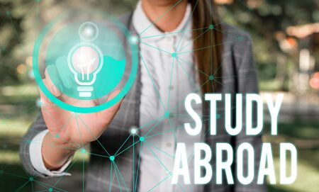 Handwriting text Study Abroad. Conceptual photo Pursuing educational opportunities in a foreign country Female human wear formal work suit presenting presentation use smart device