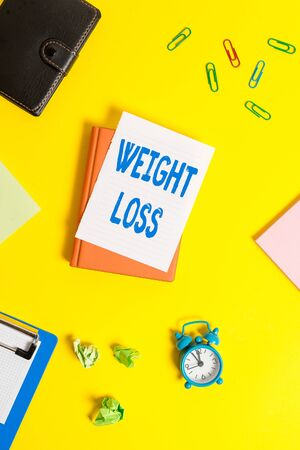 Text sign showing Weight Loss. Business photo showcasing Decrease in Body Fluid Muscle Mass Reduce Fat Dispose Tissue Pile of empty papers with copy space on the table