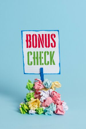 Word writing text Bonus Check. Business photo showcasing something in addition to what is expected or strictly due Reminder pile colored crumpled paper clothespin reminder blue background
