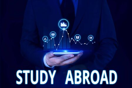 Text sign showing Study Abroad. Business photo showcasing Pursuing educational opportunities in a foreign country Male human wear formal work suit presenting presentation using smart device Фото со стока