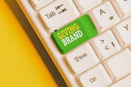Conceptual hand writing showing Giving Brand. Concept meaning The process of giving a Name to a company products or services White pc keyboard with note paper above the white background