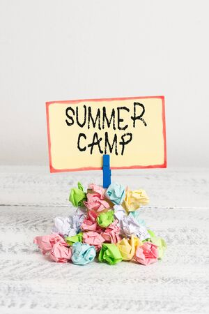 Writing note showing Summer Camp. Business concept for Supervised program for kids and teenagers during summertime. Reminder pile colored crumpled paper clothespin wooden space