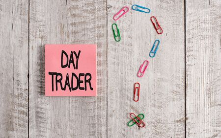Writing note showing Day Trader. Business concept for A demonstrating that buy and sell financial instrument within the day Pastel colour note paper placed next to stationary above wooden table