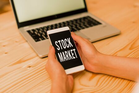 Handwriting text Stock Market. Conceptual photo Particular market where stocks and bonds are traded or exhange woman laptop computer smartphone mug office supplies technological devices
