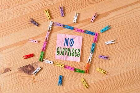 Text sign showing No Surprises. Business photo showcasing Presupposed Eventual Destined Traditional Set The Usual Colored clothespin papers empty reminder wooden floor background office