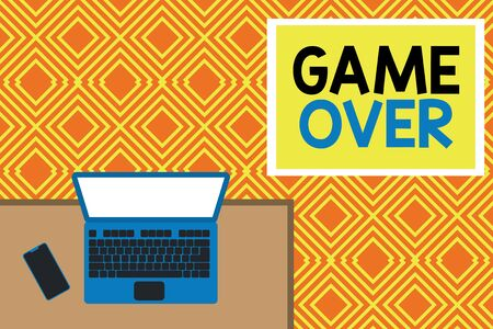 Conceptual hand writing showing Game Over. Concept meaning A situation in a particular sport that reach his finals or ending Office working place laptop lying wooden desk smartphone