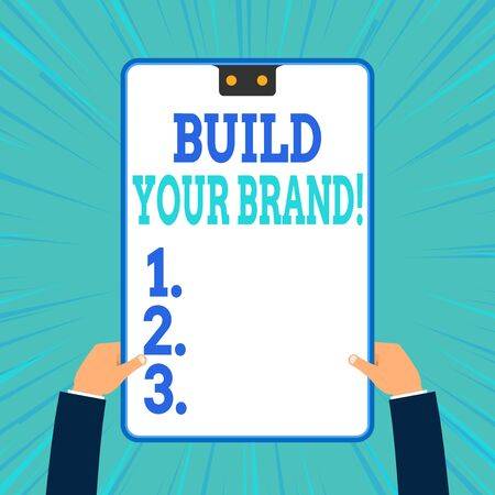 Conceptual hand writing showing Build Your Brand. Concept meaning creates or improves customers knowledge and opinions of product Two male hands holding electronic device geometrical background
