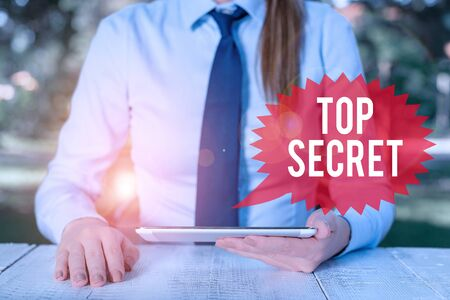 Word writing text Top Secret. Business photo showcasing telling someone important data or information that he cant tell Female business person sitting by table and holding mobile phone