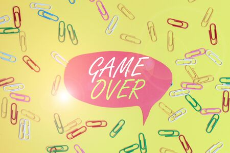 Handwriting text Game Over. Conceptual photo A situation in a particular sport that reach his finals or ending Flat lay above empty paper with copy space and colored paper clips Imagens