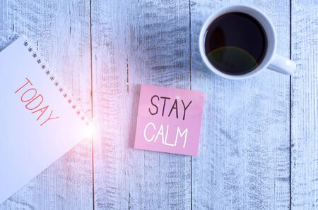 Conceptual hand writing showing Stay Calm. Concept meaning Maintain in a state of motion smoothly even under pressure Stationary placed next to a coffee cup above wooden table 免版税图像