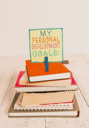 Word writing text My Personal Development Goals. Business photo showcasing Desires Wishes Career Business planning pile stacked books notebook pin clothespin colored reminder white wooden