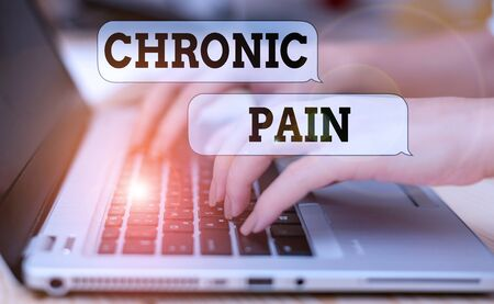 Writing note showing Chronic Pain. Business concept for pain that is ongoing and usually lasts longer than six months woman with laptop smartphone and office supplies technology Banco de Imagens