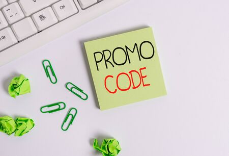 Handwriting text Promo Code. Conceptual photo digital numbers that give you good discount on certain product Square empty green note paper with pencil on the white background and pc keyboard Archivio Fotografico