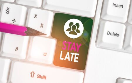Text sign showing Stay Late. Business photo text A routine in which a demonstrating goes to somewhere out of time White pc keyboard with empty note paper above white background key copy space Stock Photo