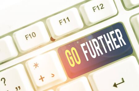 Text sign showing Go Further. Business photo showcasing To move to a greater distance or overcome your limitations White pc keyboard with empty note paper above white background key copy space