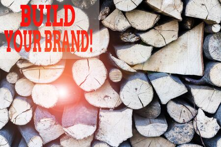 Text sign showing Build Your Brand. Business photo showcasing creates or improves customers knowledge and opinions of product Background dry chopped firewood logs stacked up in a pile winter chimney