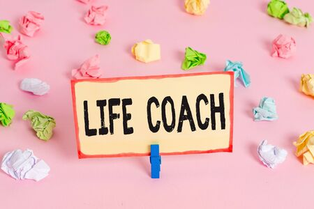 Conceptual hand writing showing Life Coach. Concept meaning A demonstrating who advices clients how to solve their problems or goals Colored crumpled papers empty reminder pink floor clothespin