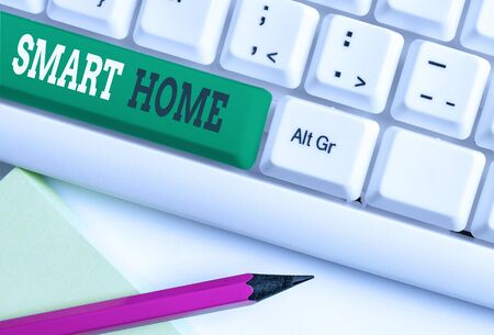 Conceptual hand writing showing Smart Home. Concept meaning automation system control lighting climate entertainment systems White pc keyboard with note paper above the white background