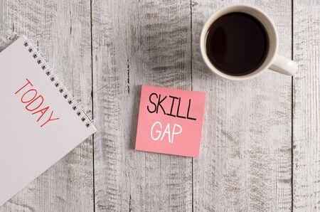 Konzeptionelle Handschrift zeigt Skill Gap. Begriff Sinne, die sich auf eine demonstrierende s beziehen, ist Schwäche oder Einschränkung des Wissens stationär neben einer Kaffeetasse über dem Holztisch platziert?