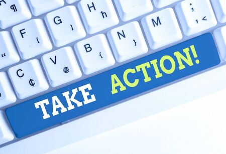 Conceptual hand writing showing Take Action. Concept meaning do something official or concerted to achieve aim with problem White pc keyboard with note paper above the white background Reklamní fotografie