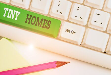 Conceptual hand writing showing Tiny Homes. Concept meaning houses contain one room only or two and small entrance Cheap White pc keyboard with note paper above the white background Stock Photo