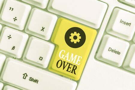 Conceptual hand writing showing Game Over. Concept meaning A situation in a particular sport that reach his finals or ending White pc keyboard with note paper above the white background