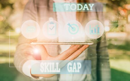 Text sign showing Skill Gap. Business photo showcasing Refering to a demonstrating s is weakness or limitation of knowlege Female human wear formal work suit presenting presentation use smart device