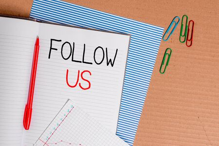 Writing note showing Follow Us. Business concept for Act of demonstrating to invite an individual or group to join his company Striped paperboard notebook cardboard office study supplies chart paper