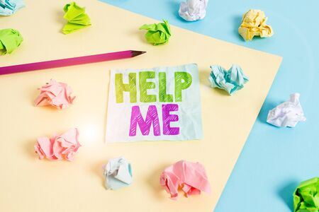 Handwriting text Help Me. Conceptual photo Asking someone to assist you Shouting for it Teamwork Volunteer Colored crumpled papers empty reminder blue yellow background clothespin