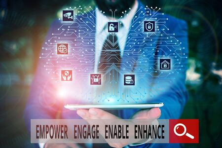 Conceptual hand writing showing Empower Engage Enable Enhance. Concept meaning Empowerment Leadership Motivation Engagement Male wear formal work suit presenting presentation smart device