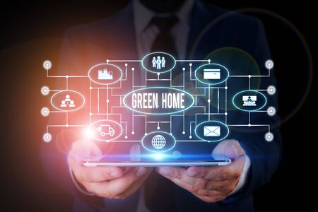 Handwriting text writing Green Home. Conceptual photo An area filled with plants and trees where you can relax Male human wear formal work suit presenting presentation using smart device