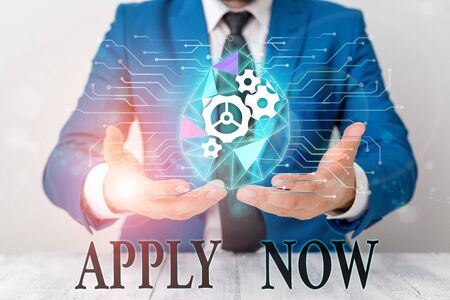 Writing note showing Apply Now. Business concept for An act of a demonstrating to acquire the job related to the profession Male human wear formal suit presenting using smart device Imagens