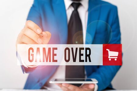 Word writing text Game Over. Business photo showcasing A situation in a particular sport that reach his finals or ending Businessman pointing with pen in empty copy space