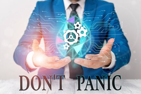 Writing note showing Don T Panic. Business concept for sudden strong feeling of fear prevents reasonable thought Male human wear formal suit presenting using smart device 写真素材